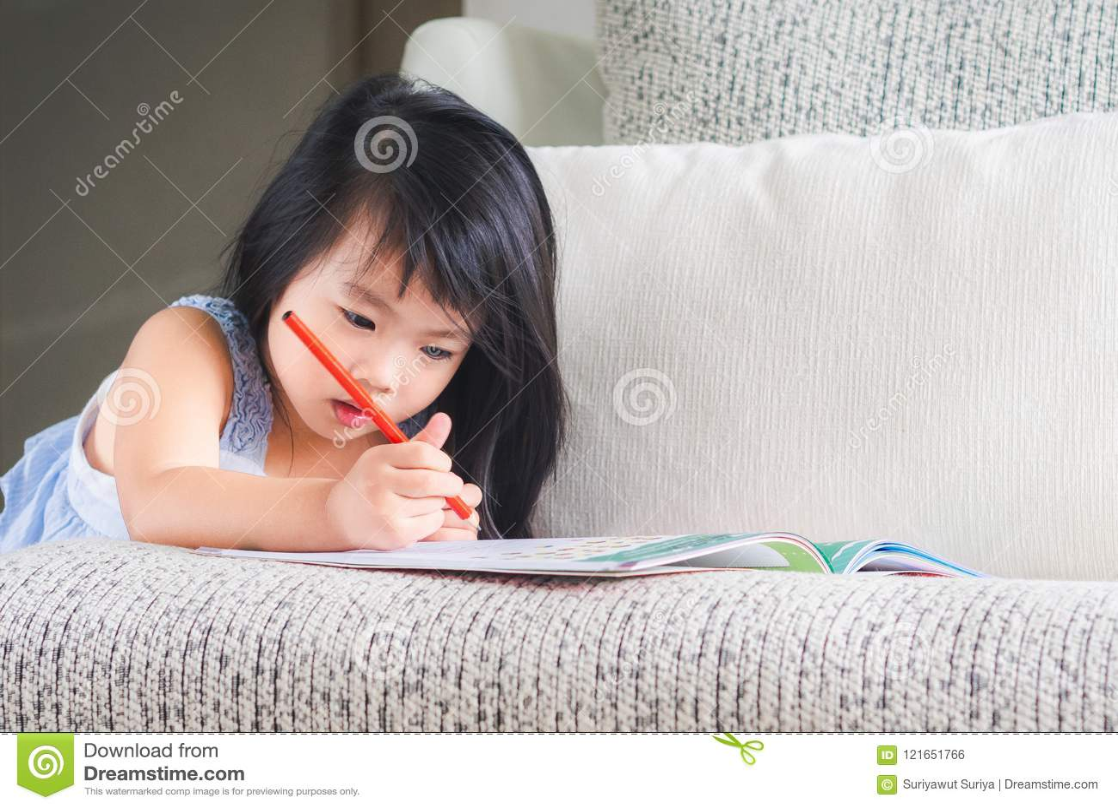 La piccola ragazza sveglia felice sta scrivendo il libro con la matita rossa sul Th