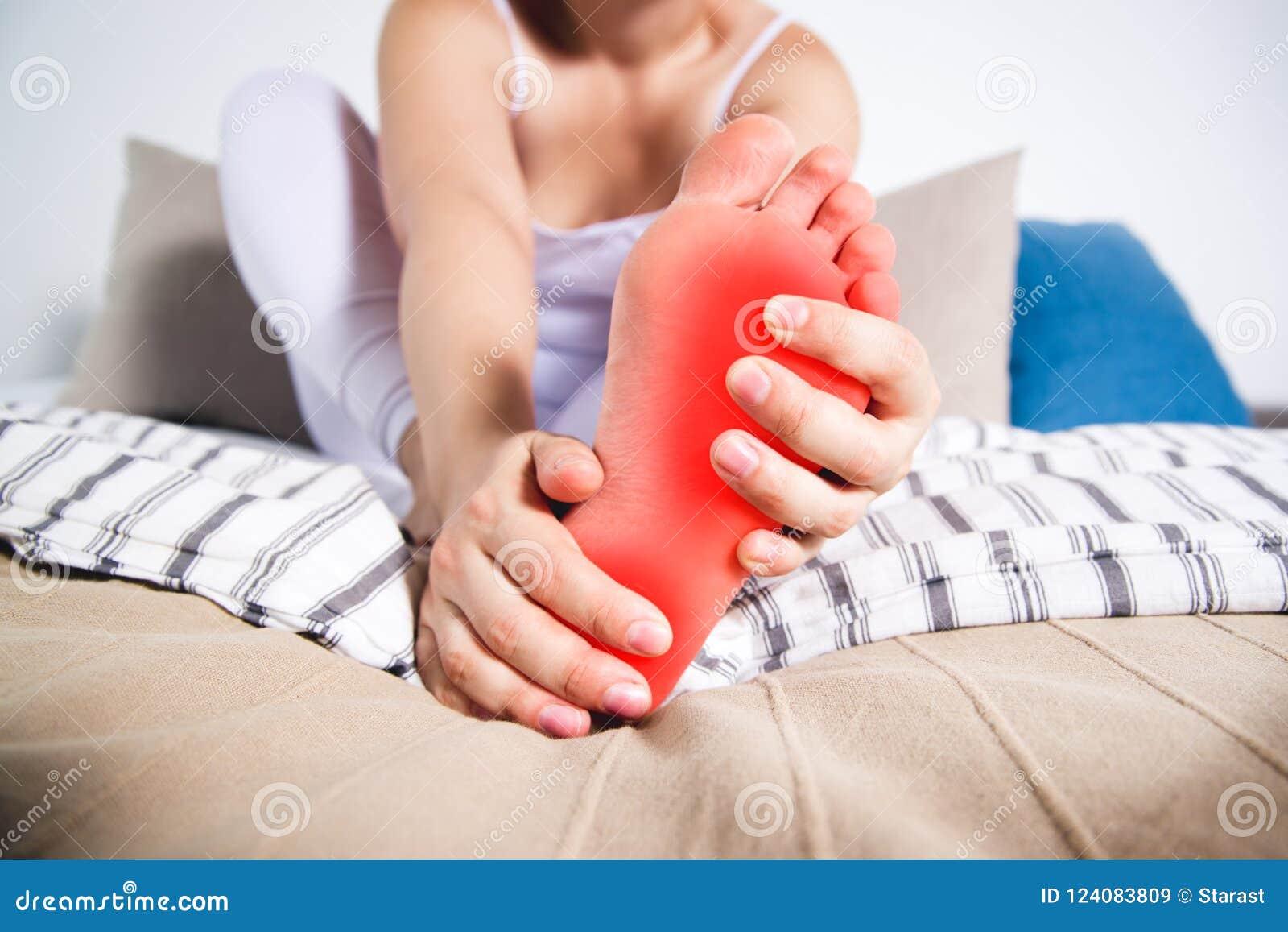 La pierna del ` s de la mujer daña, el dolor en el pie, masaje de pies femeninos