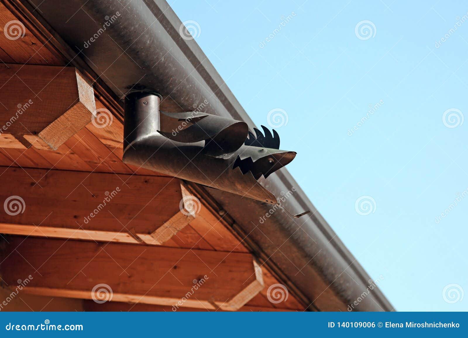 La pieza del tejado con forma de los pescados del canal del metal Casa de madera debajo del cielo azul Detalle constructivo del a