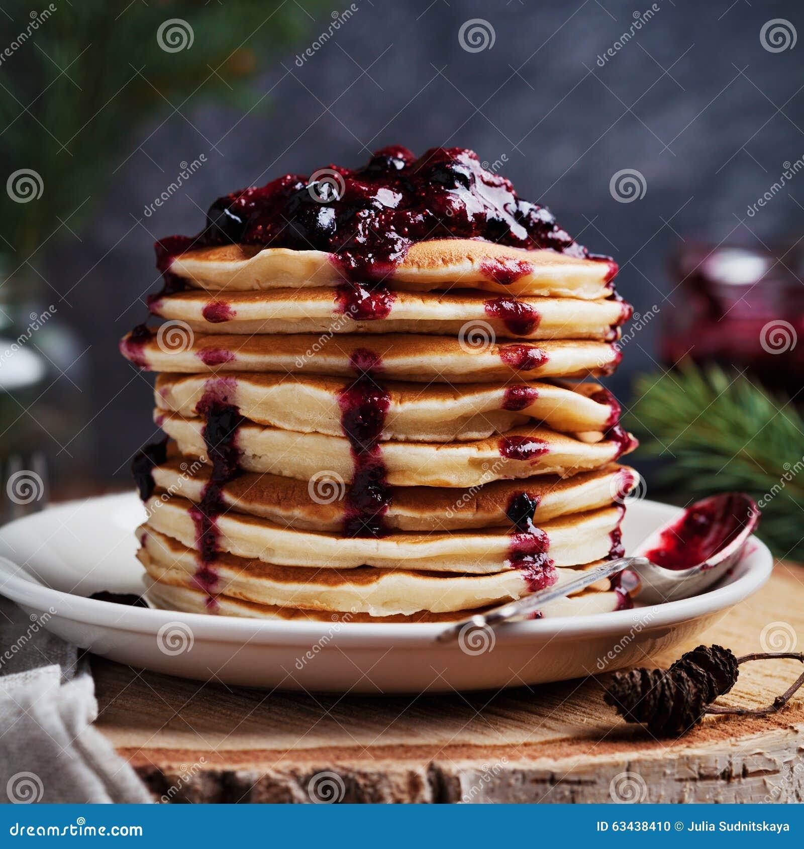 La pila de crepes americanas o los buñuelos con la fresa y el arándano atasca en la placa blanca en la Navidad adornada tabla rús