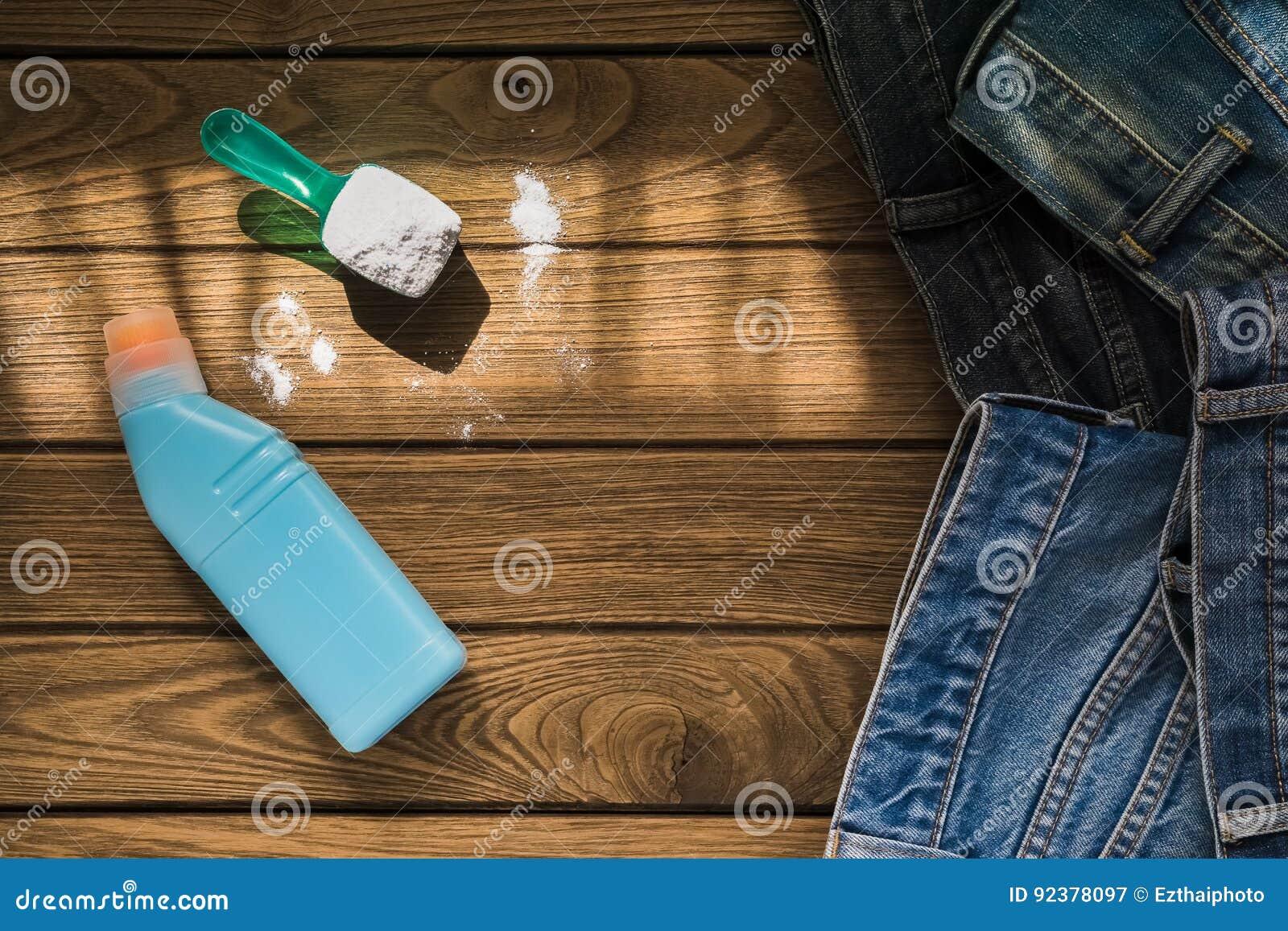 La pila de tejanos viste con el detergente y el detergente encendido