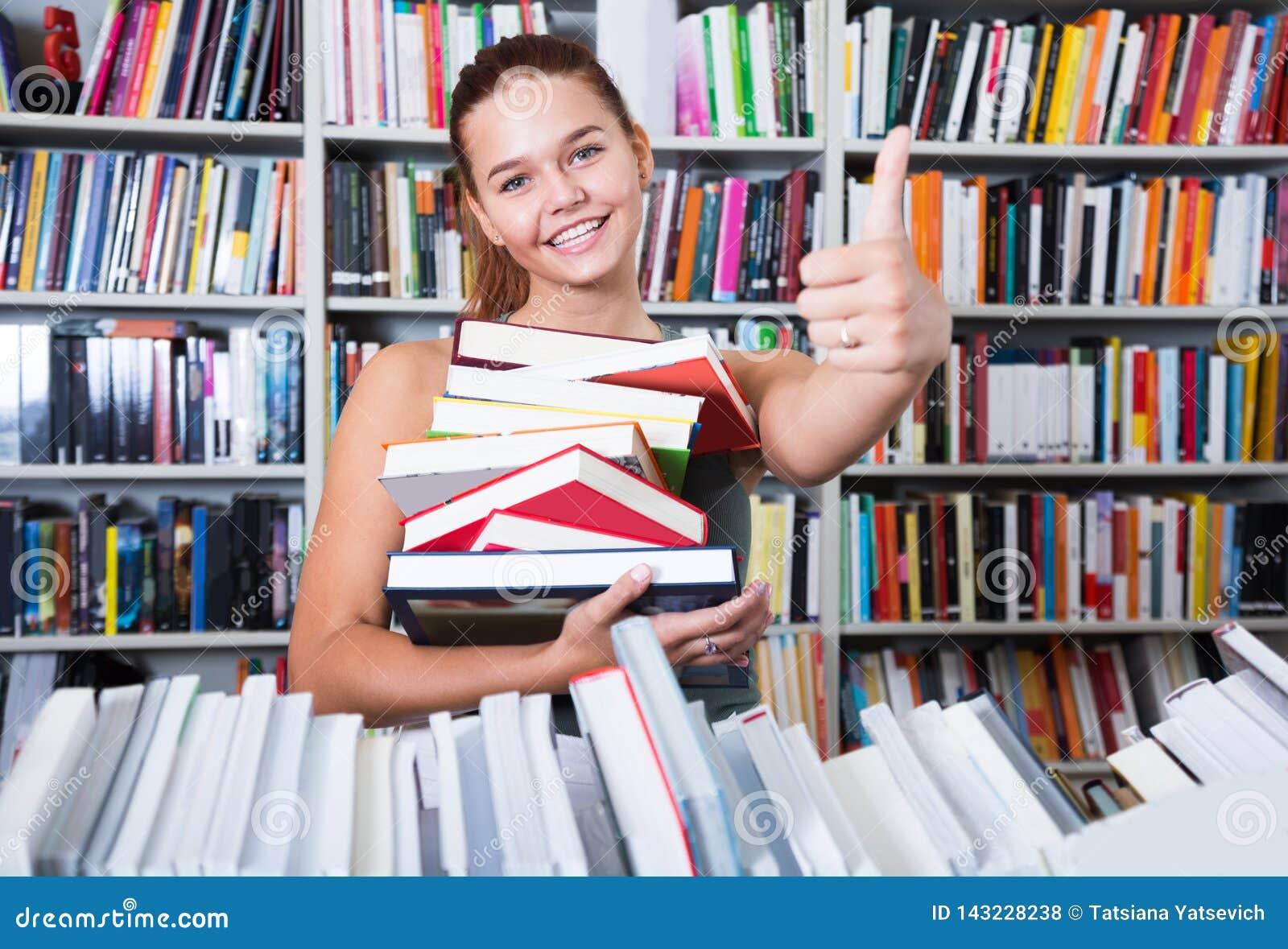 La pila de la tenencia de la muchacha del adolescente de demostraciones de los libros golpea pesadamente para arriba en una libre