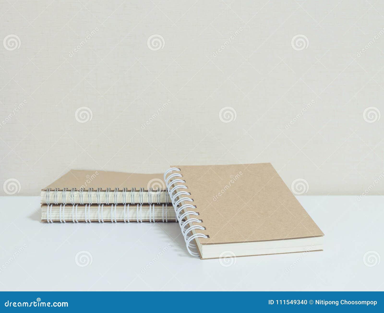 La pila del primer de cuaderno marrón en el escritorio y el papel pintado blancos en sitio texturizó el fondo con el espacio de l