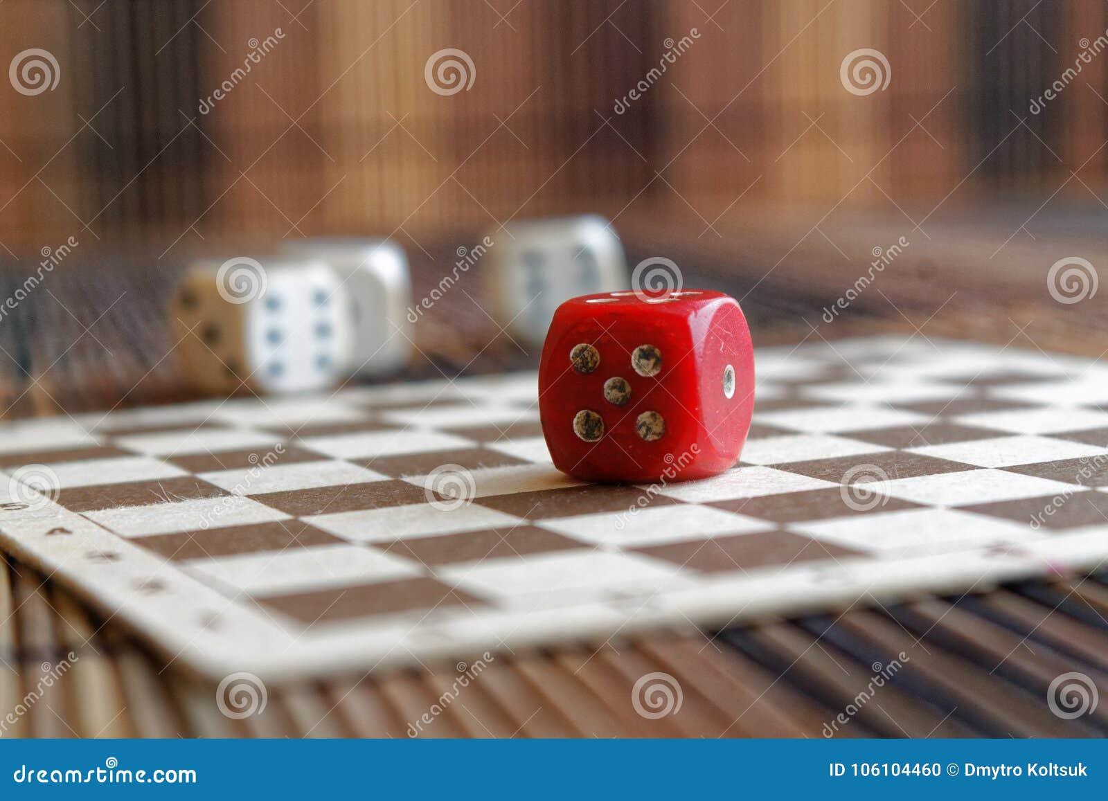 La pile de plastique de trois blancs découpe et une matrice rouge sur le fond brun de conseil en bois Six cubes en côtés avec les