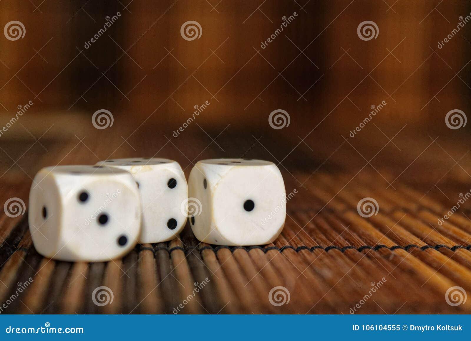 La pile de plastique de trois blancs découpe sur le fond brun de conseil en bois Six cubes en côtés avec les points noirs Numéro