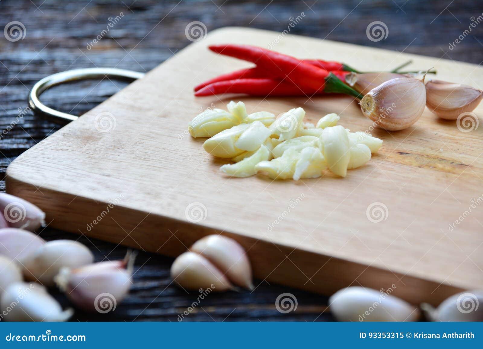 La pimienta y el ajo de chile de las especias pusieron a la tabla de cortar de madera en el wo