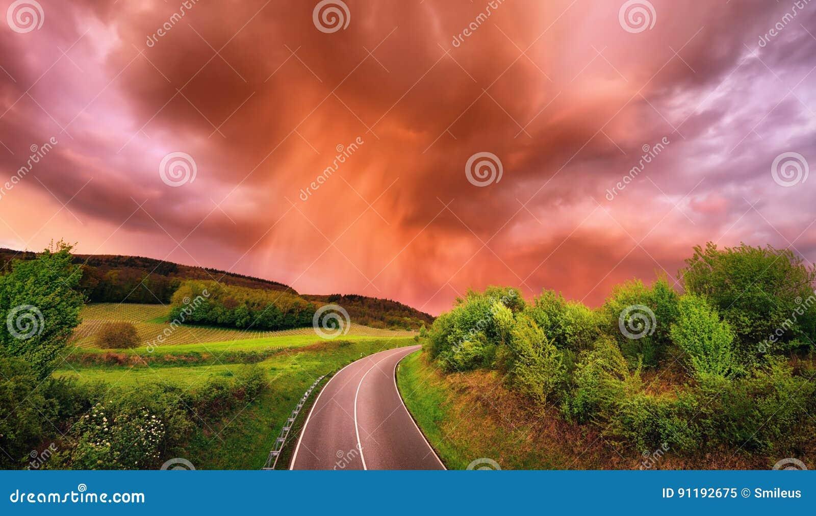 La pioggia affascinante si rannuvola una strada al tramonto