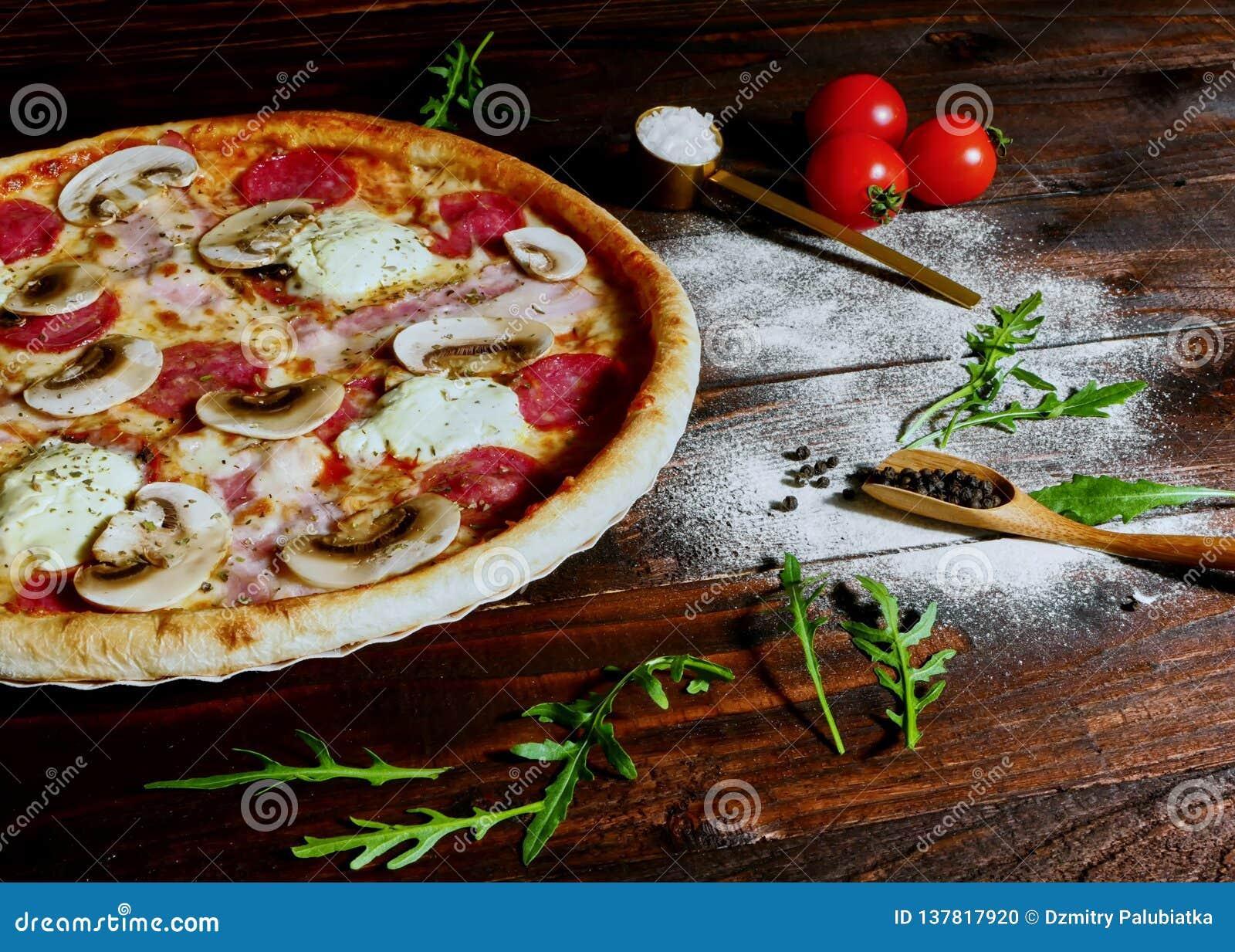 La pizza casalinga del prosciutto, del salame e del fungo è servito su un bordo su un vecchio tavolo da cucina di legno rustico c