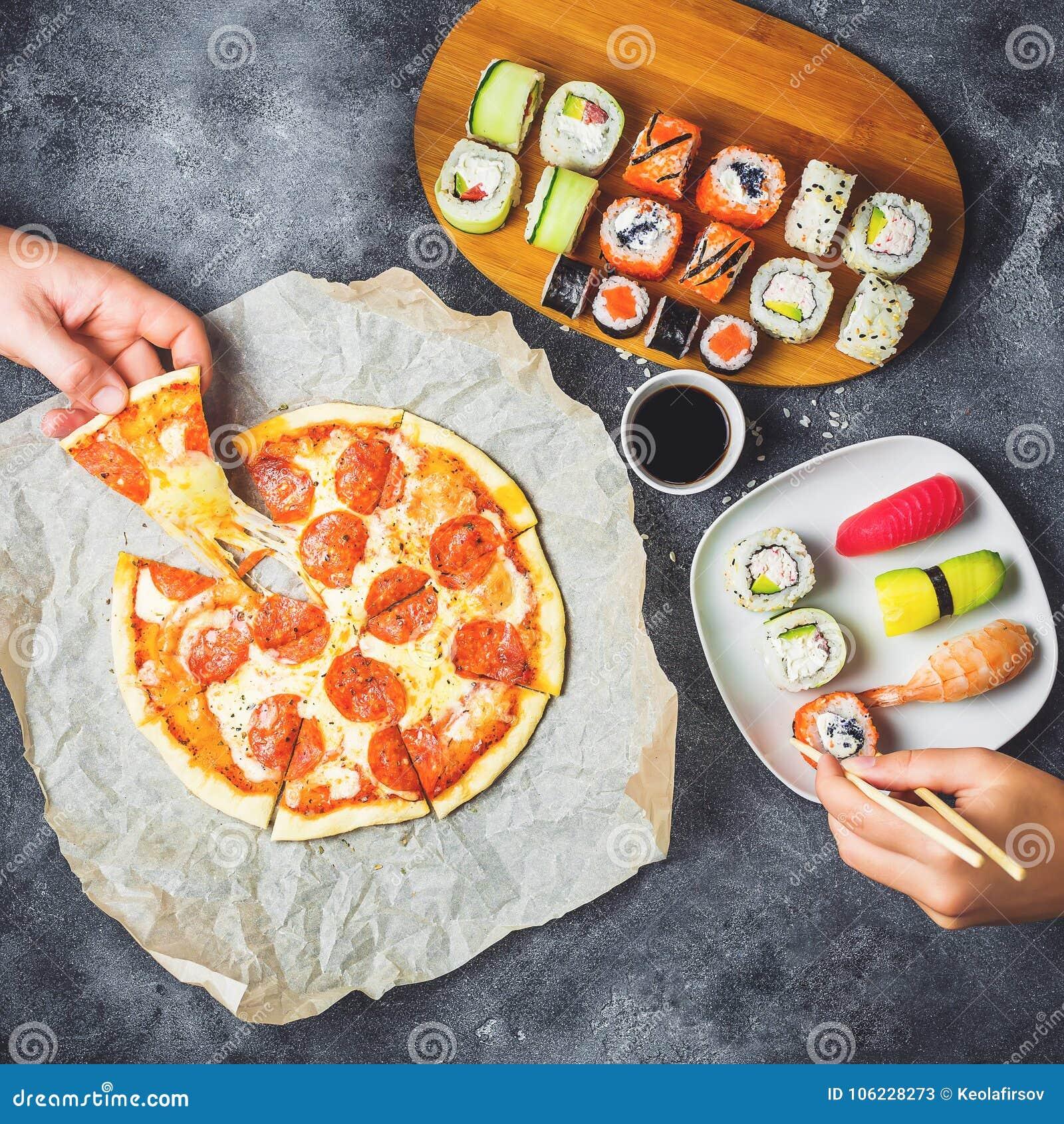 La pizza sabrosa con el salami, el sistema de rollos de sushi y las manos toman la comida Fondo oscuro Endecha plana, visión supe
