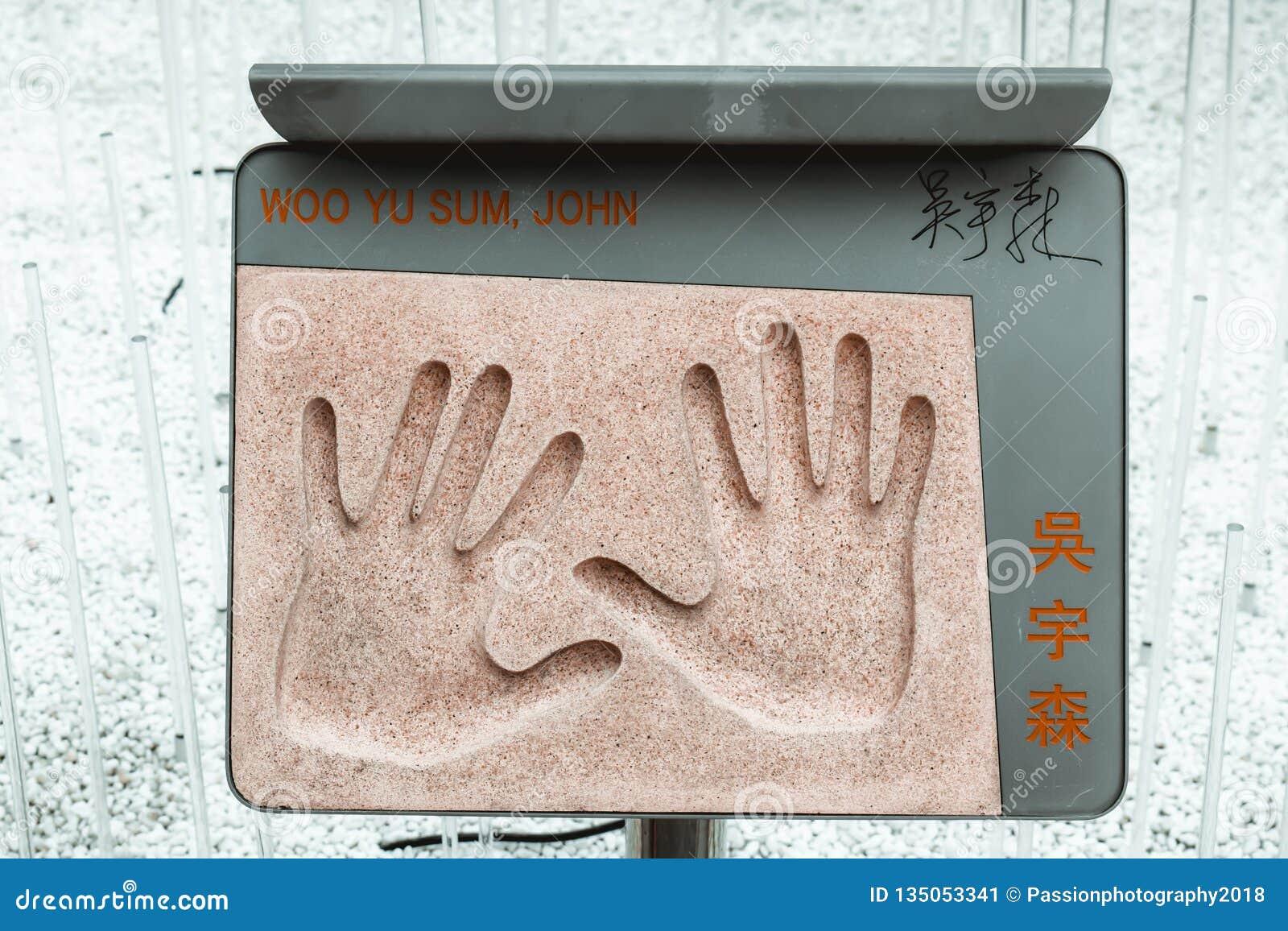 La placa con la impresión de la mano de director de película chino legendario de acción John Woo colocó en el jardín de estrellas