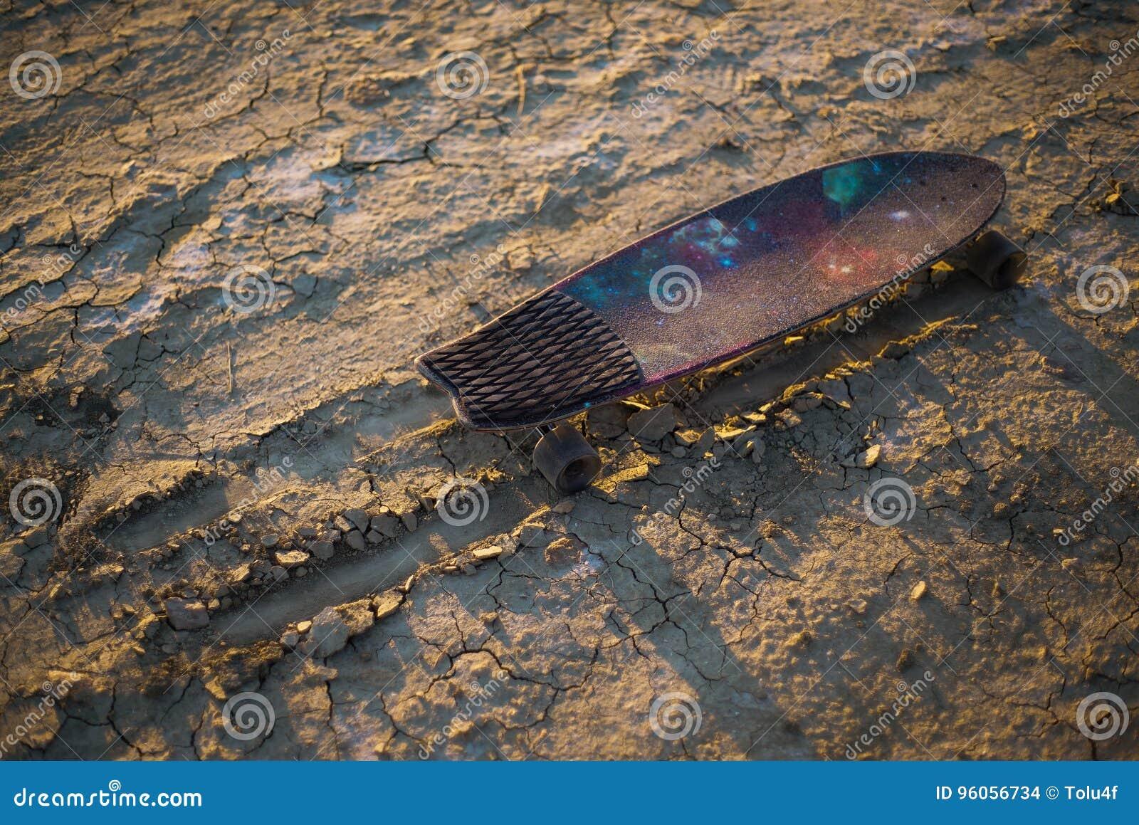 La planche à roulettes ou le longboard a collé dans le sable dans le désert au coucher du soleil