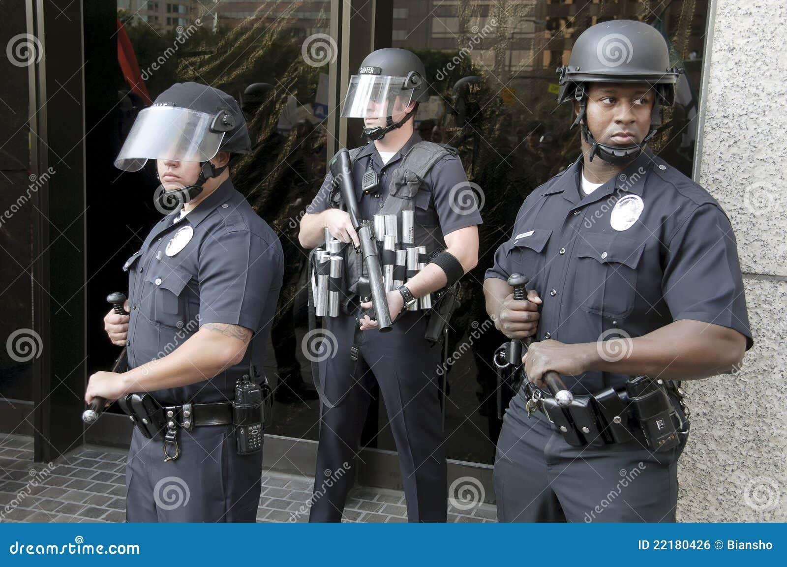 La policía de alboroto coloca al protector durante ocupa la marcha del LA
