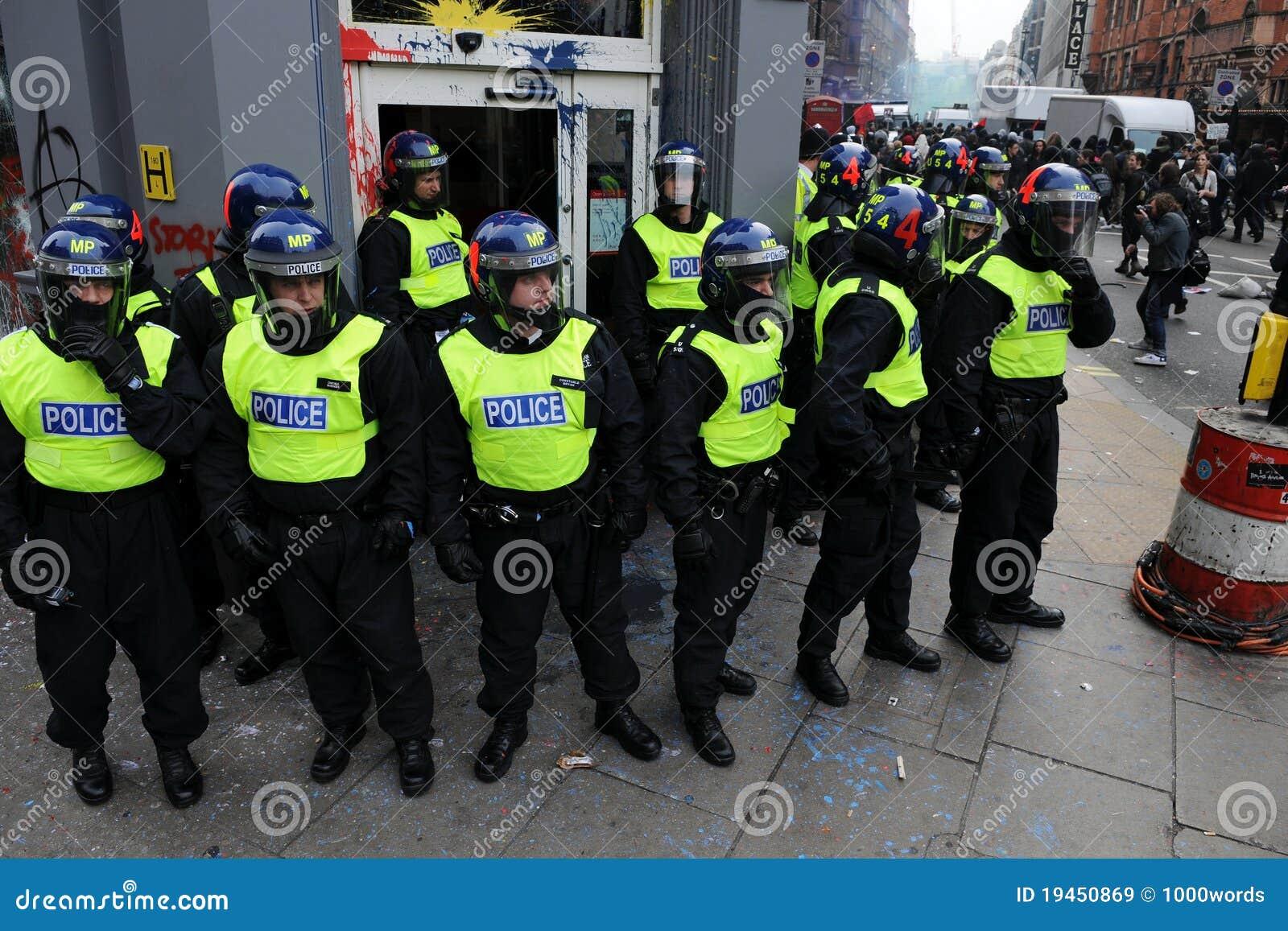 La policía de alboroto guarda una batería en el alboroto en Londres