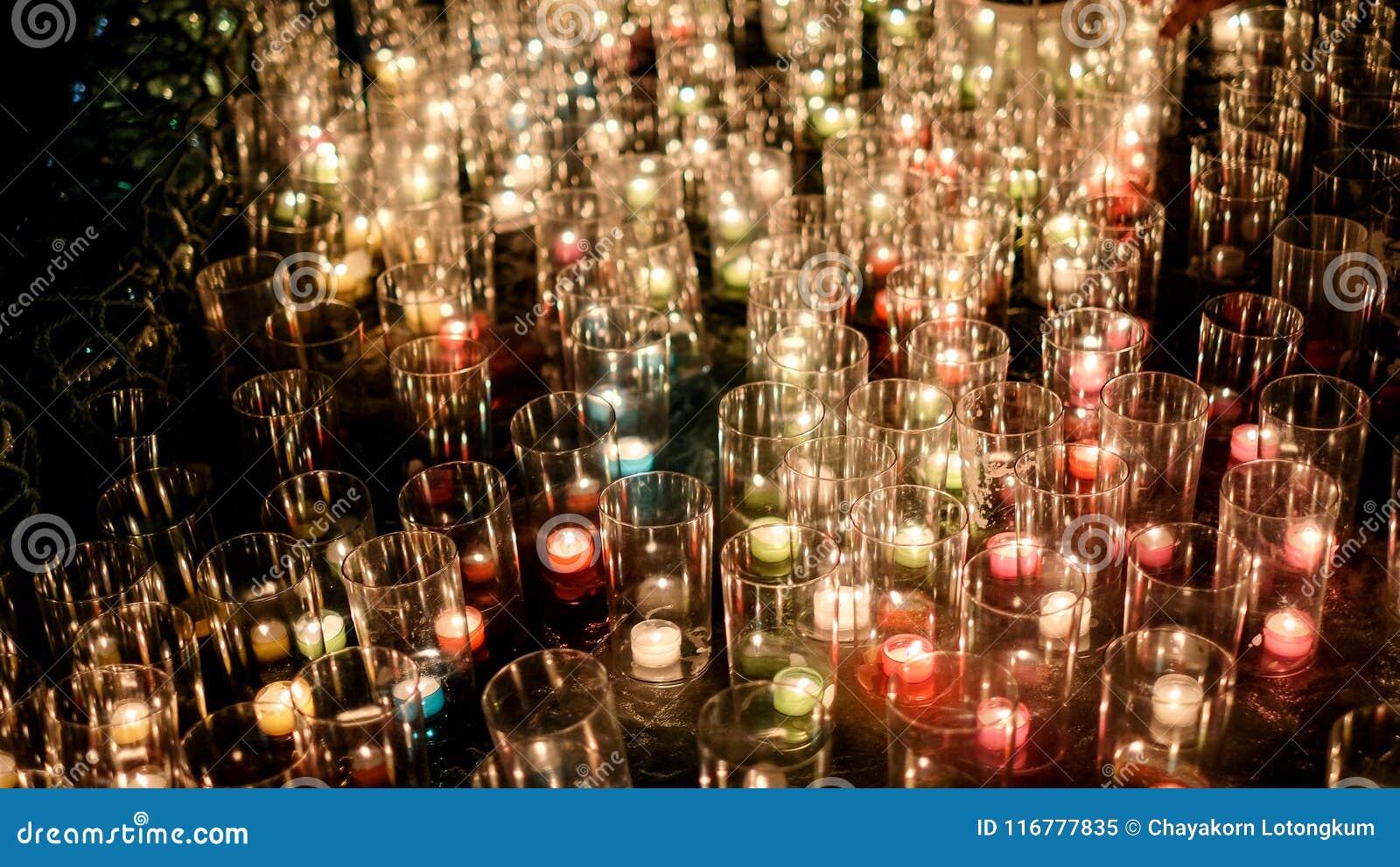 La porción de hierba y la luz del fuego de la vela flamean