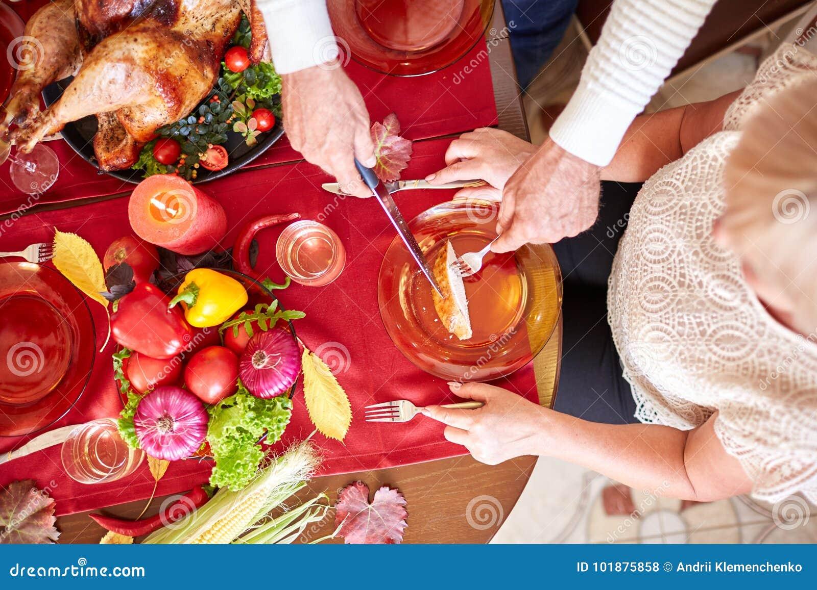 La porción del viejo hombre del primer asó el pavo en un fondo de la tabla Cena de la acción de gracias Concepto festivo tradicio