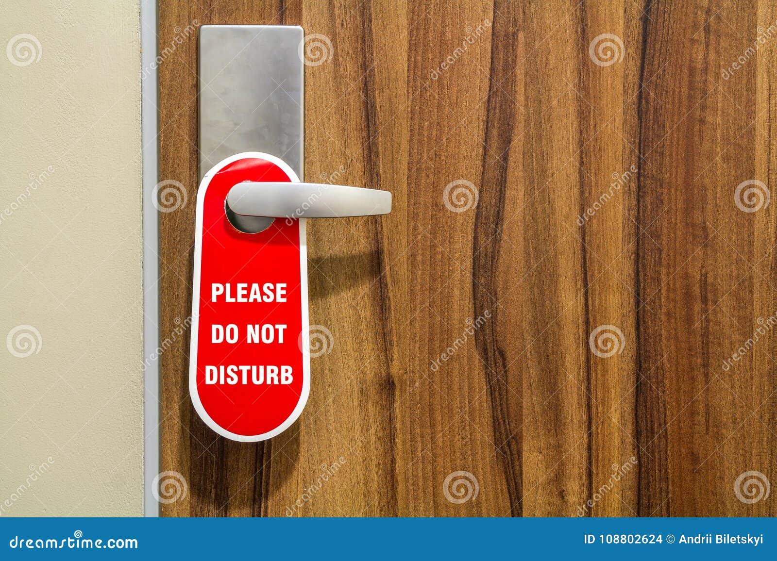 La porta di camera di albergo con il segno non disturba prego