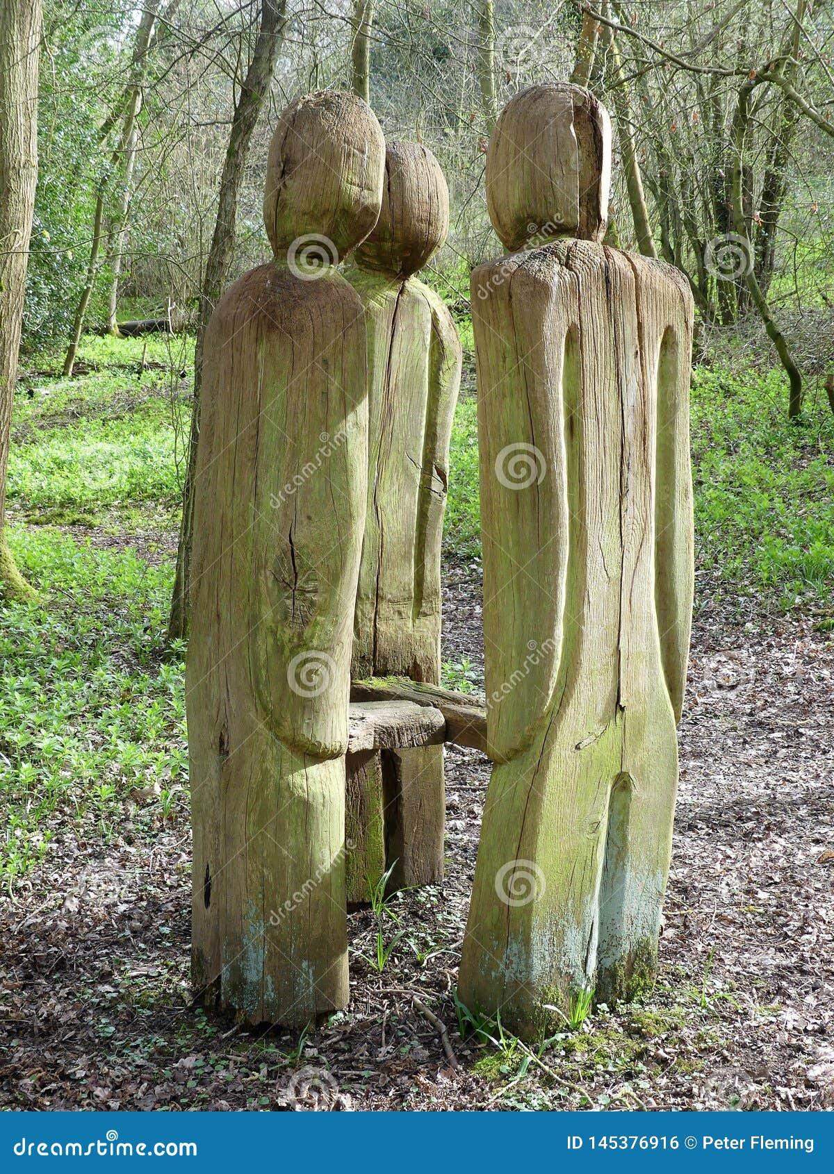 La position a découpé des figures entourant le banc sur la promenade de région boisée