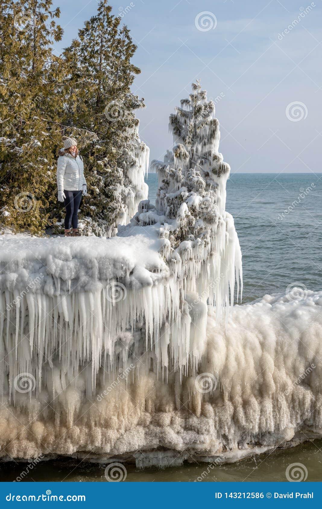 La position de femme sur la glace a couvert le plateau le long du lac Michigan au parc de point de caverne, le Wisconsin