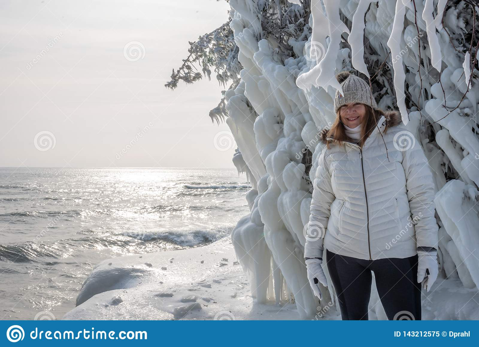 La position heureuse de personne à côté de la glace a couvert des arbres au parc de point de caverne le long du lac Michigan en h