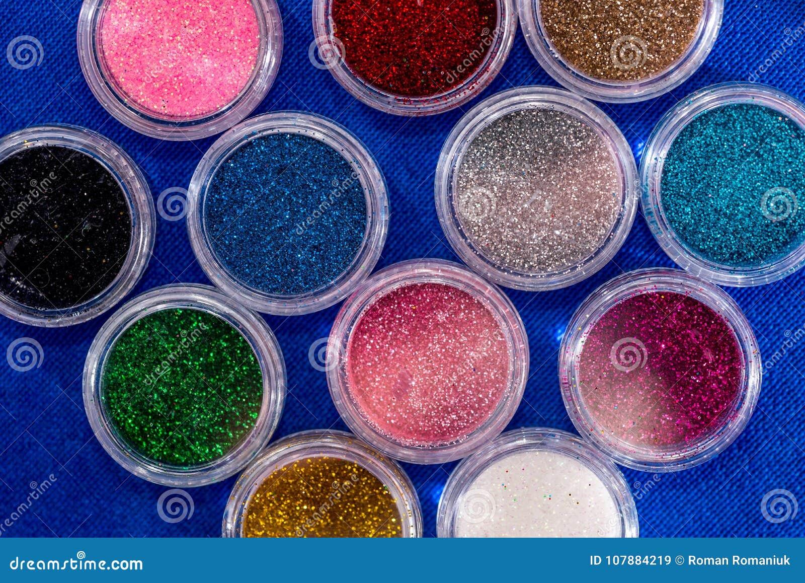 La poussière UV de poudre pour l ongle polonais sur le bleu