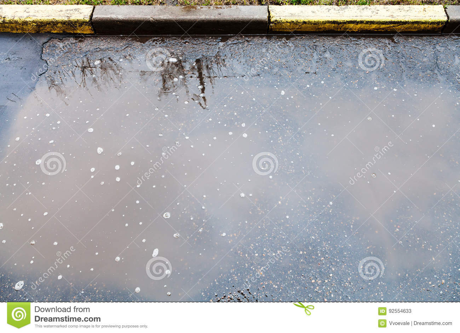 La pozza sporca su urbano streen in pioggia