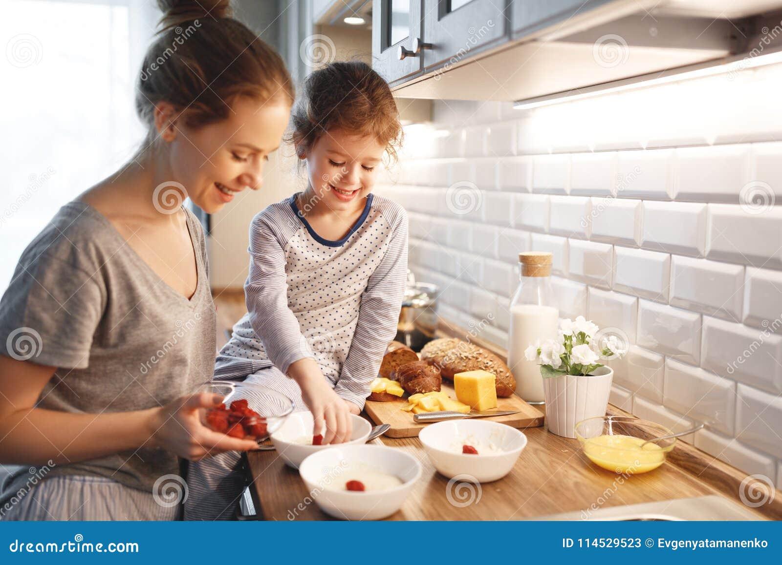La préparation de la mère de petit déjeuner de famille et la fille d enfant font cuire
