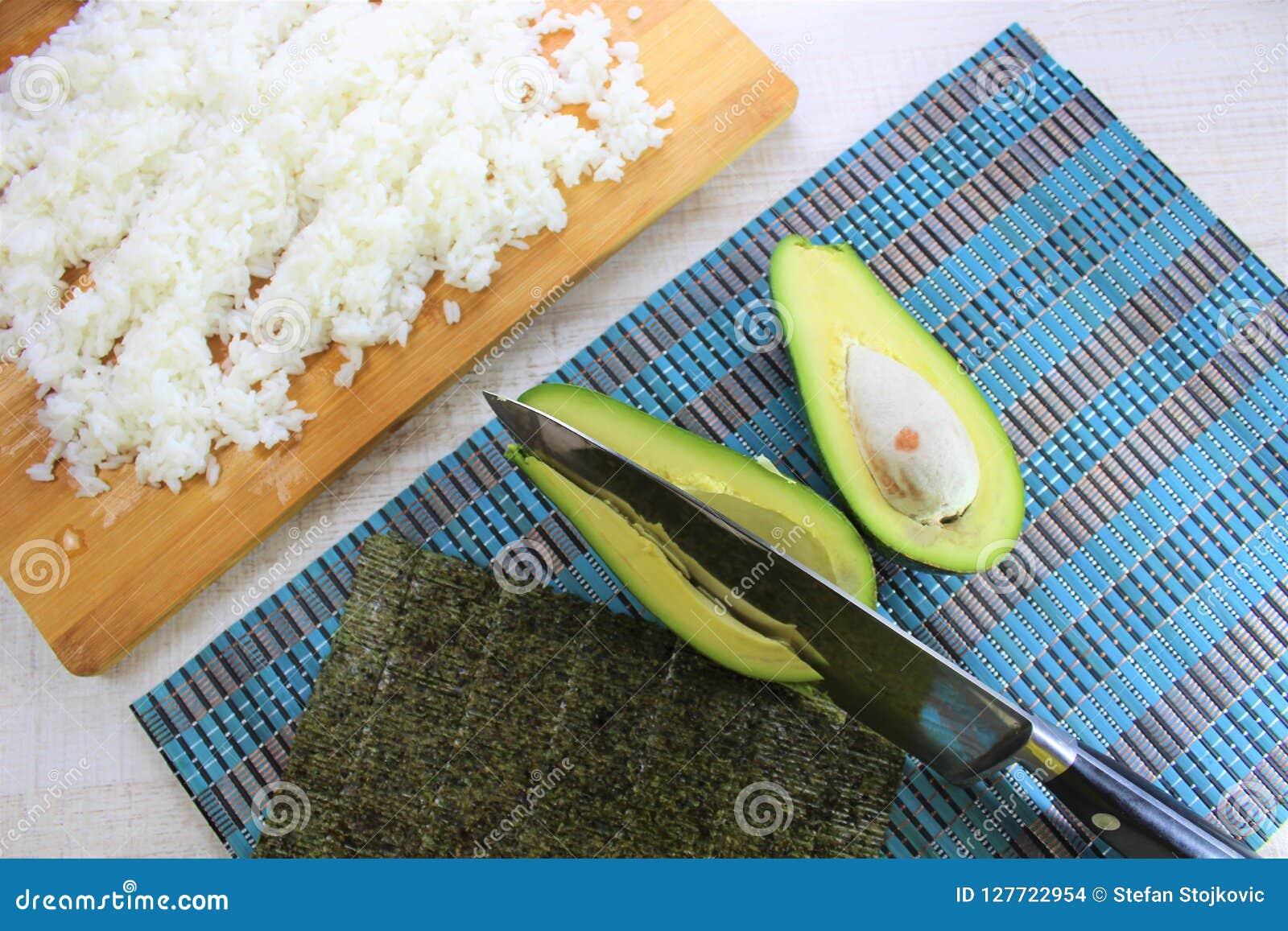 La préparation de sushi dans la cuisine, la coupe verte d avocat d ingrédients frais dans la moitié avec une algue et le blanc on