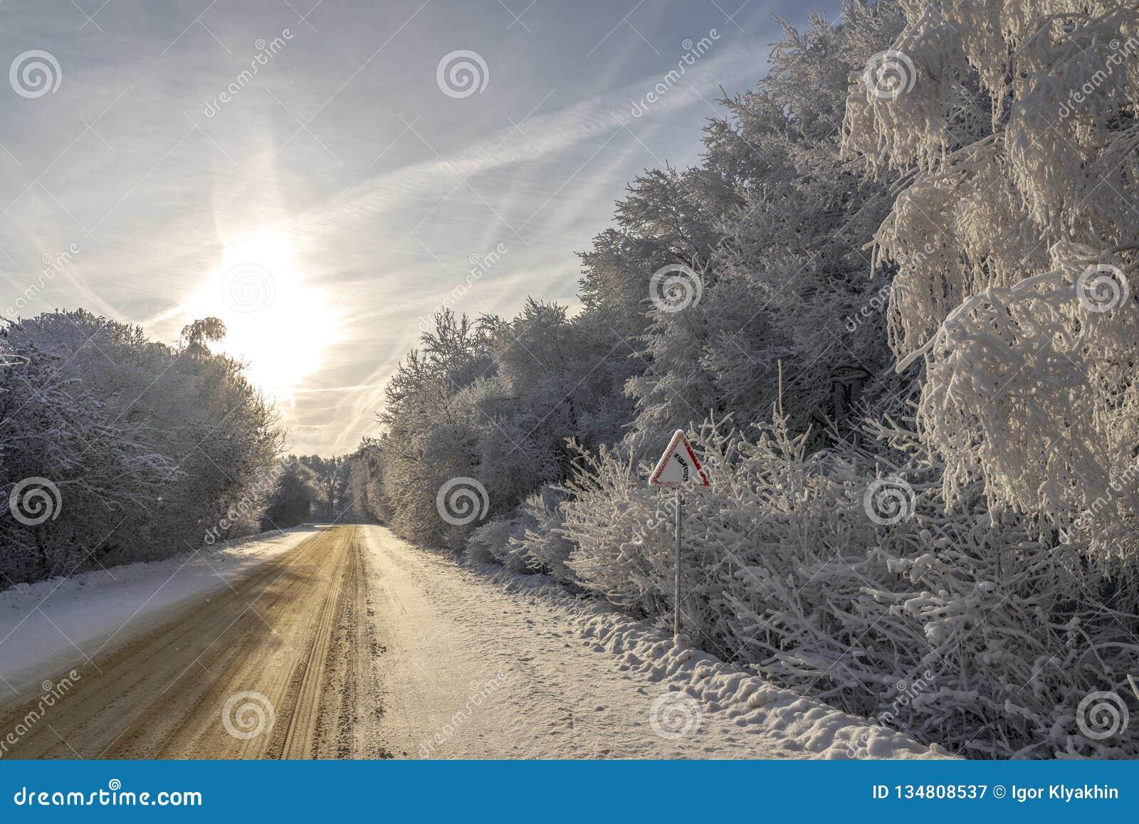 La precaución de la señal de tráfico gira el camino del invierno