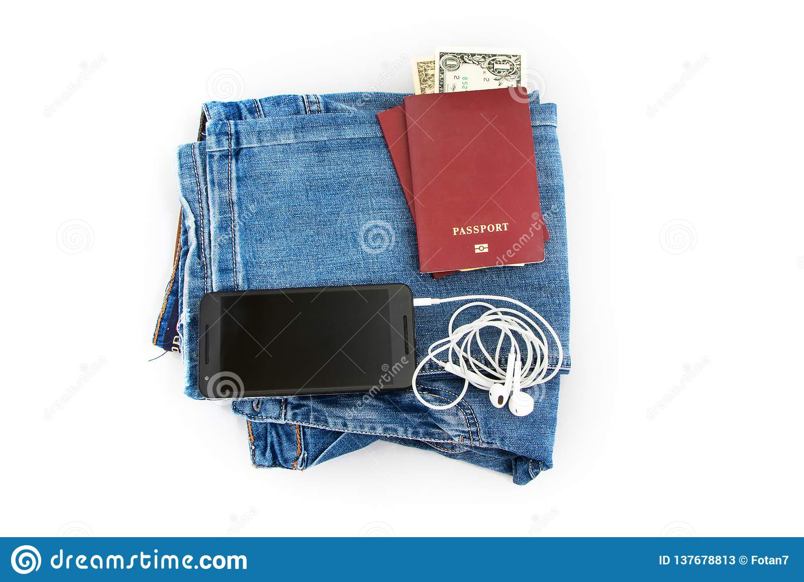 La preparazione per il viaggio, passaporto, soldi, telefono con le cuffie sui jeans ha isolato il fondo bianco