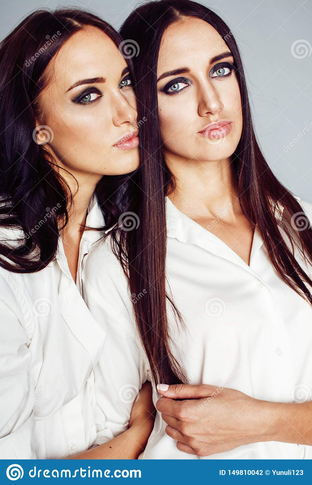 La presentaci?n de la muchacha de dos gemelos de las hermanas, haciendo el selfie de la foto, visti? la camisa blanca, amigos div