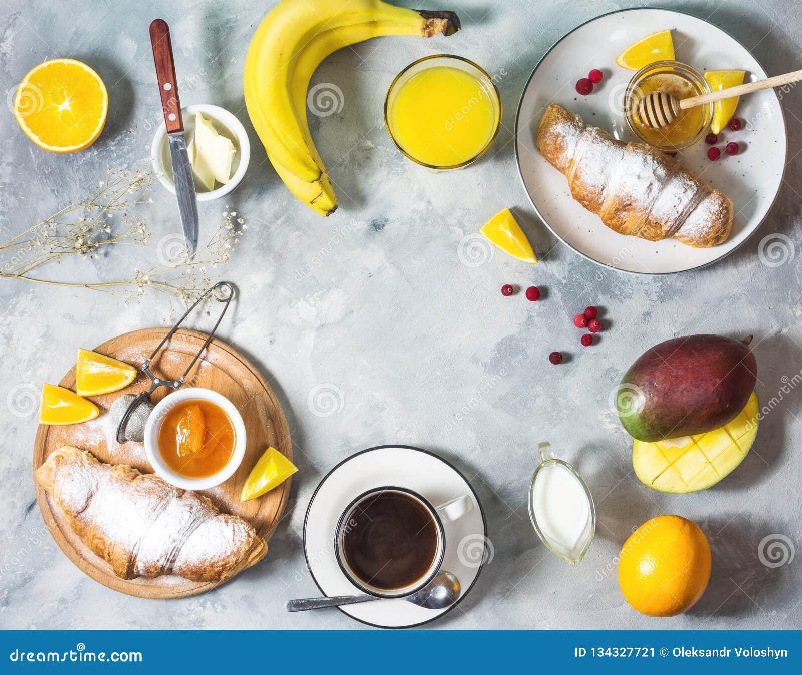 La prima colazione è servito con caffè, succo d arancia, i croissant ed i frutti su fondo concreto