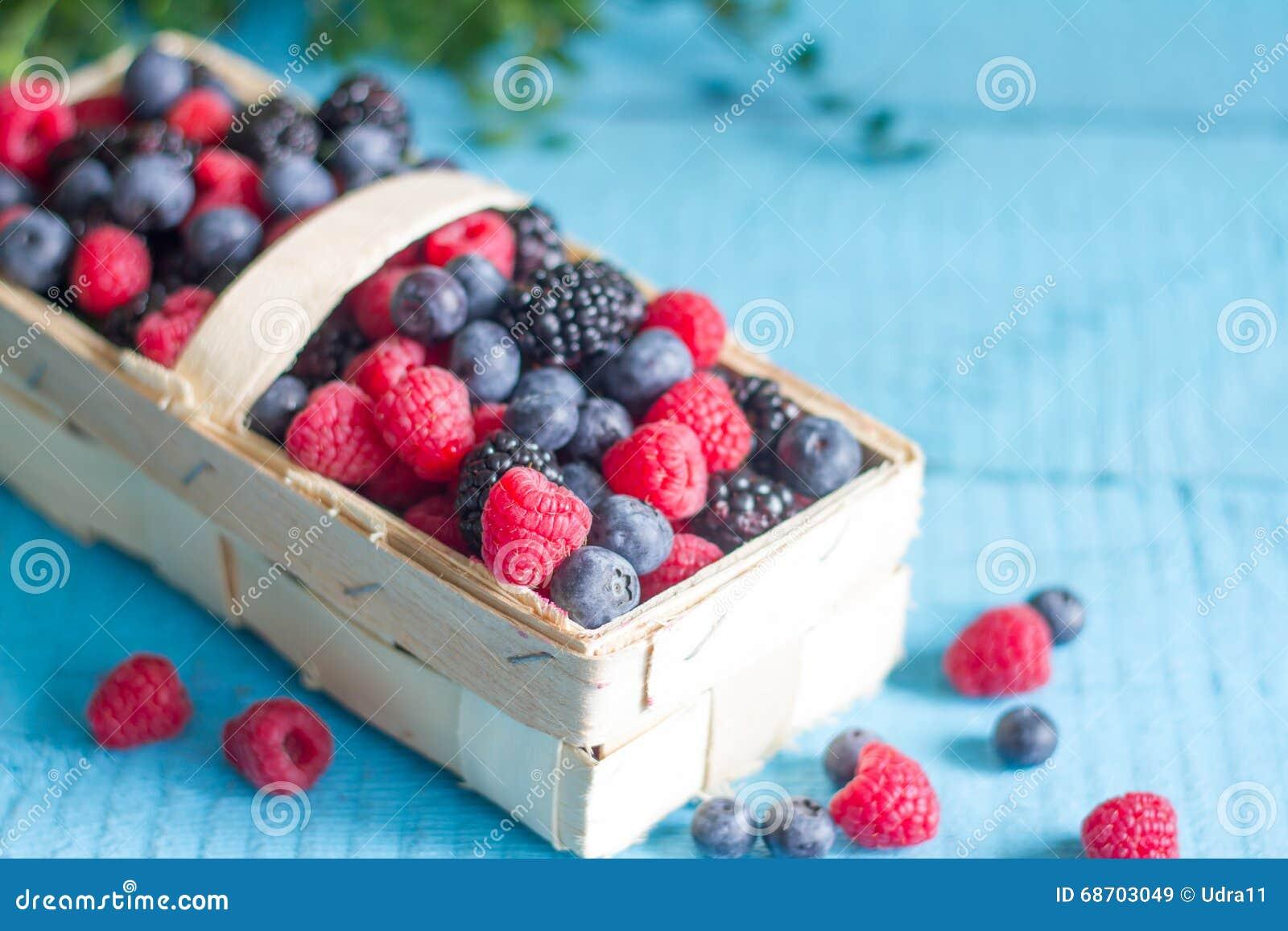 La primavera da fruto las bayas en el cestito en los tableros de madera azules