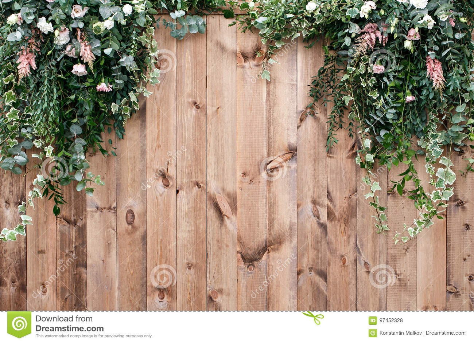La primavera fresca se pone verde con la planta de la flor blanca y de la hoja sobre el fondo de madera de la cerca