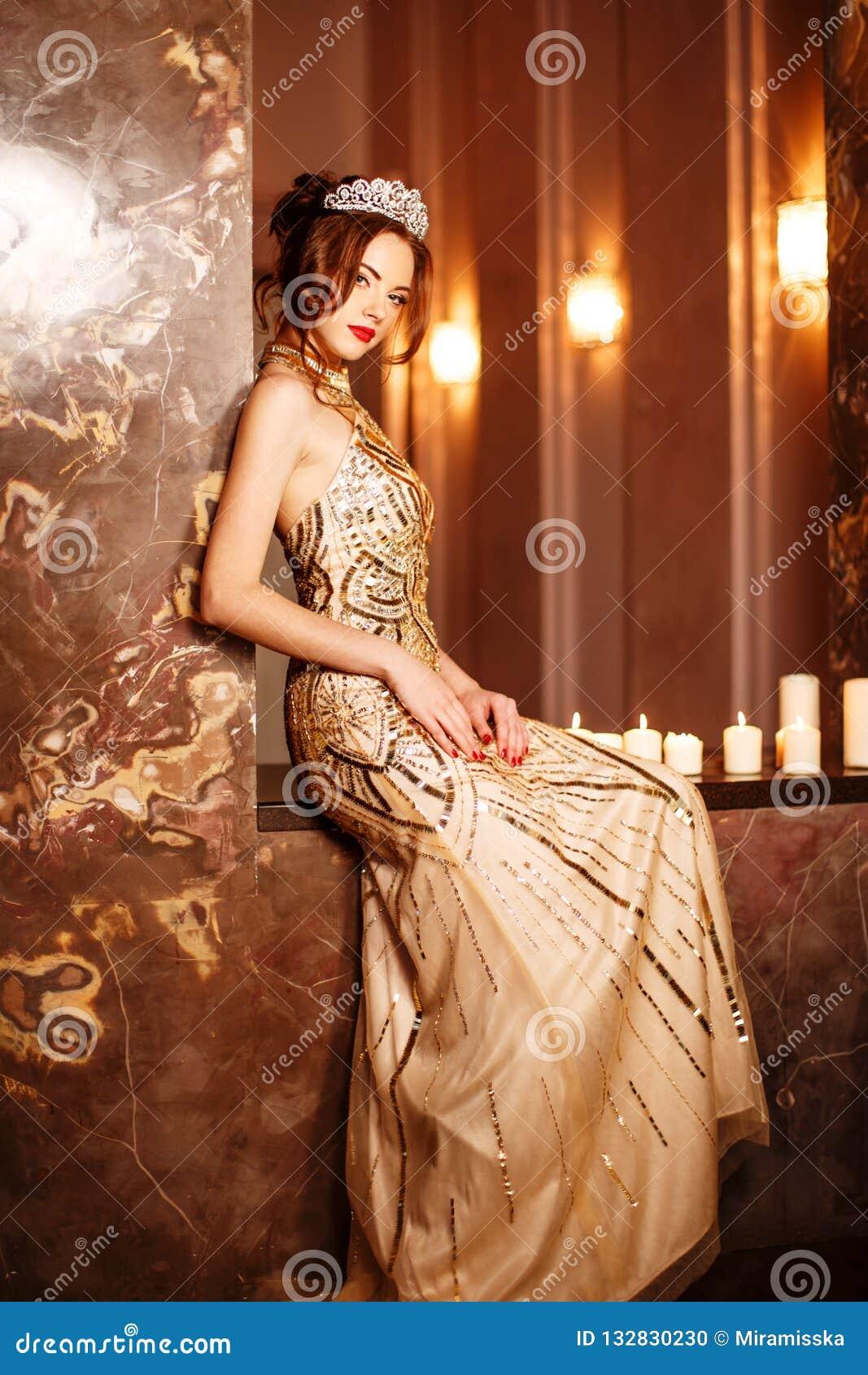 La princesa de la reina de la mujer en la corona y el vestido del lux, luces va de fiesta el backgr