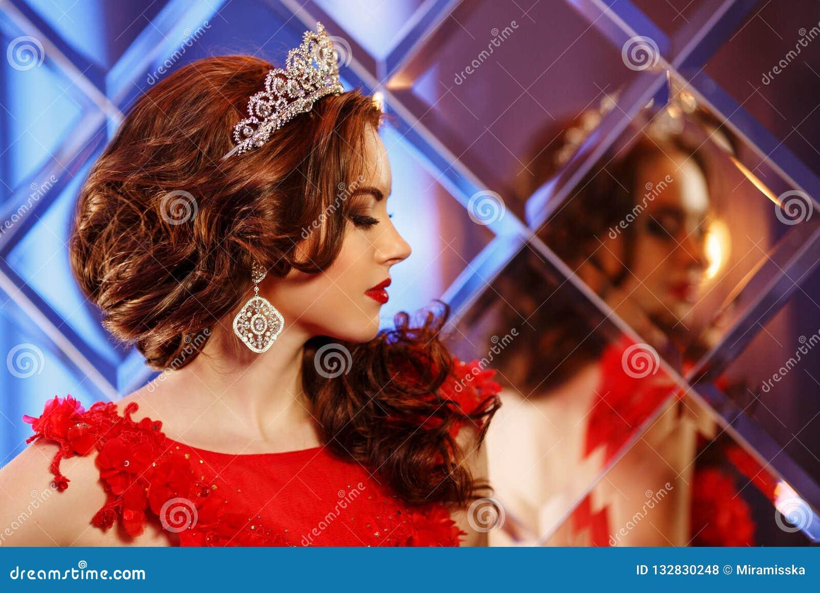 La princesse de reine de femme dans la couronne et la robe de lux, lumières font la fête le backgr