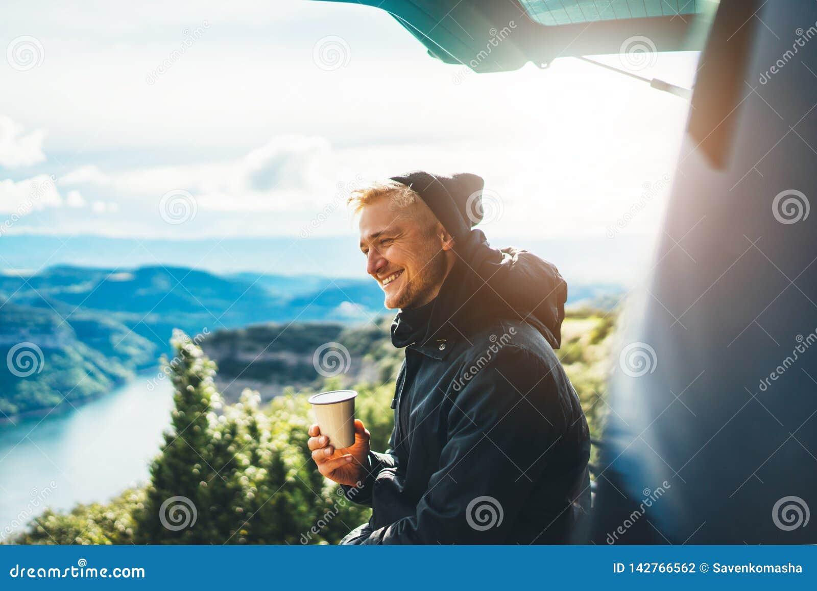La prise de touristes de hippie dans la tasse de mains de la boisson chaude, sourire isolé de type apprécient la montagne de fusé