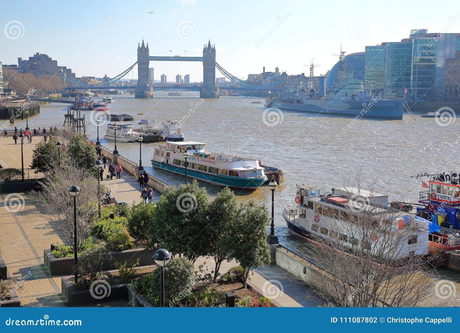 La promenade de rive est le long de la Tamise avec le pont de tour dans le fond et les péniches dedans le premier plan