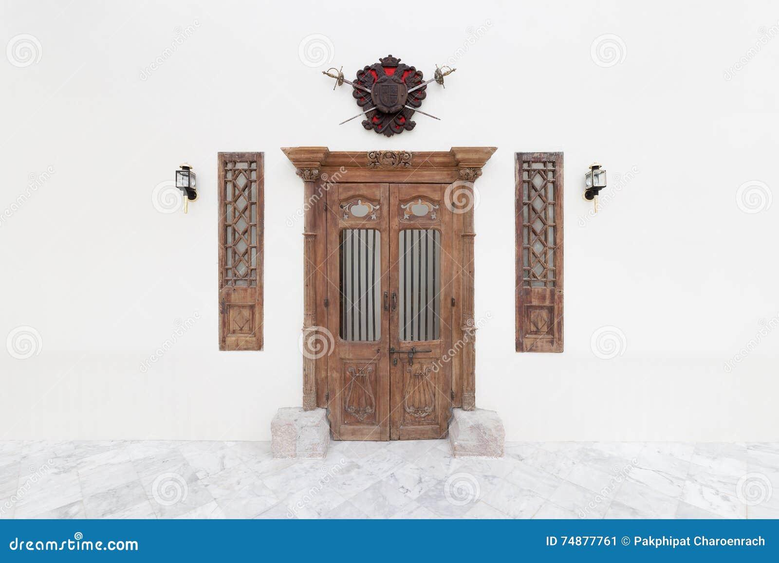 La puerta y la linterna de madera viejas en el cemento concreto blanco emparedan el backgr
