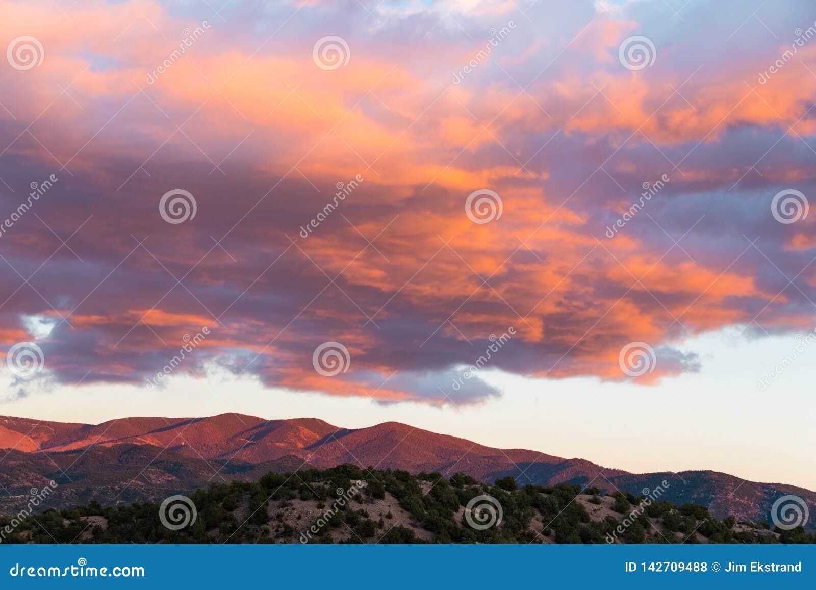 La puesta del sol hermosa echa colores púrpuras y anaranjados en las nubes y las montañas cerca de Santa Fe, New México