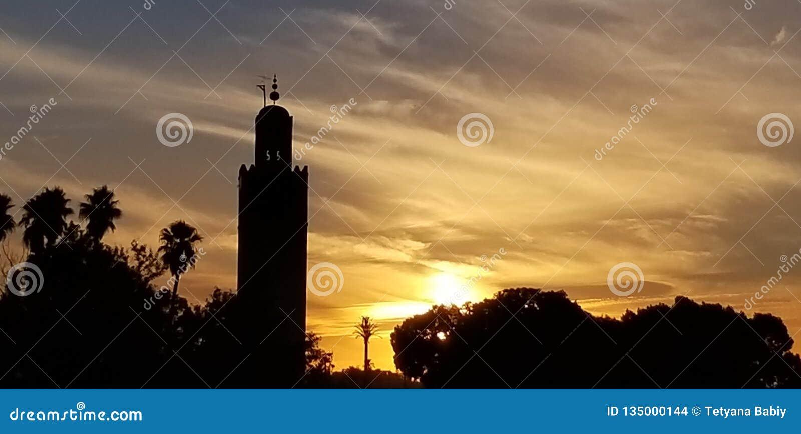 La puesta del sol por la mezquita Marrakesh, Marruecos de Koutoubia es el monumento visitado