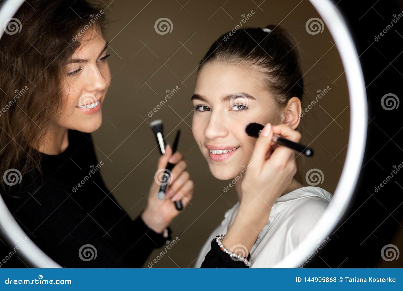 La r?flexion dans le miroir du maquilleur la fille avec du charme fait le maquillage ? une belle jeune fille