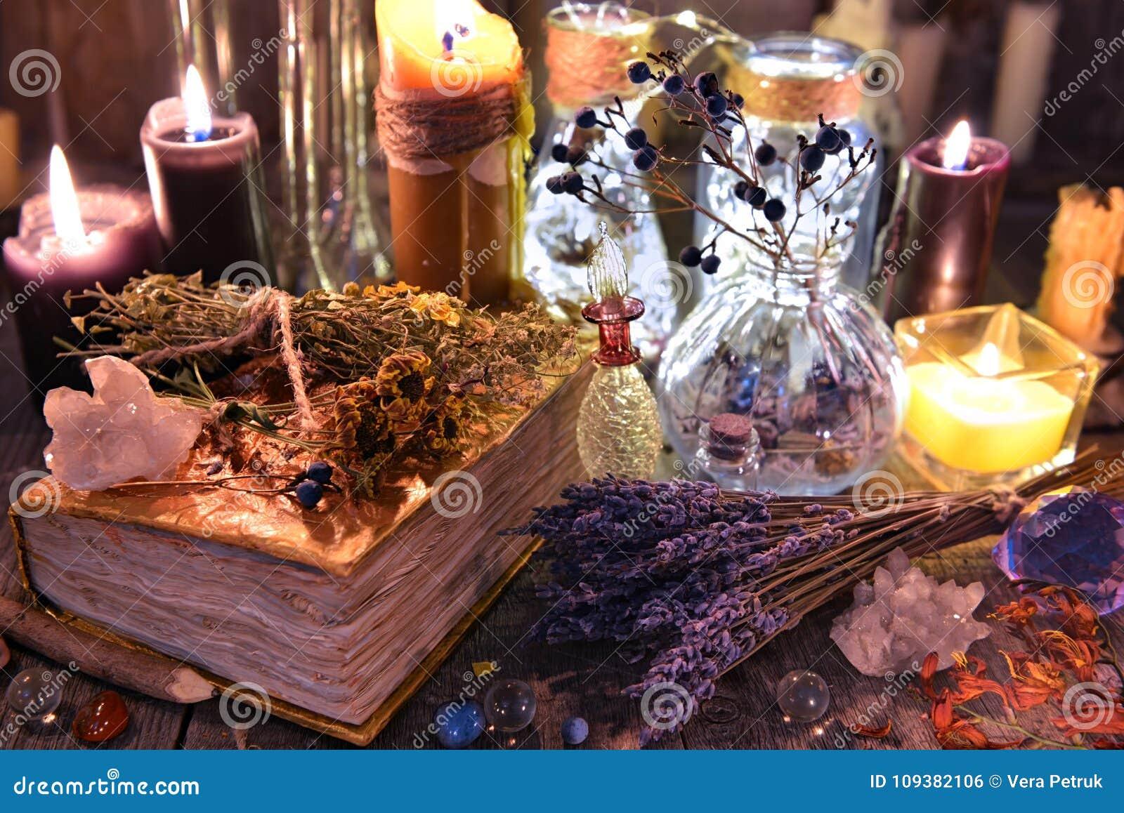 La raccolta rituale della strega con il vecchi abbecedario, lavanda, bottiglie, erbe e magia obietta