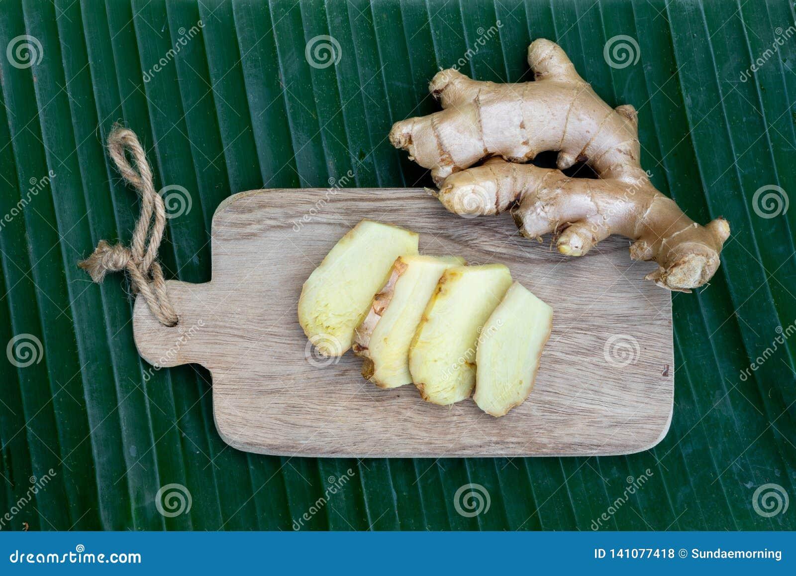 La racine de gingembre et le gingembre frais ont découpé en tranches sur le fond vert de feuille sur le fond en bois de table, co