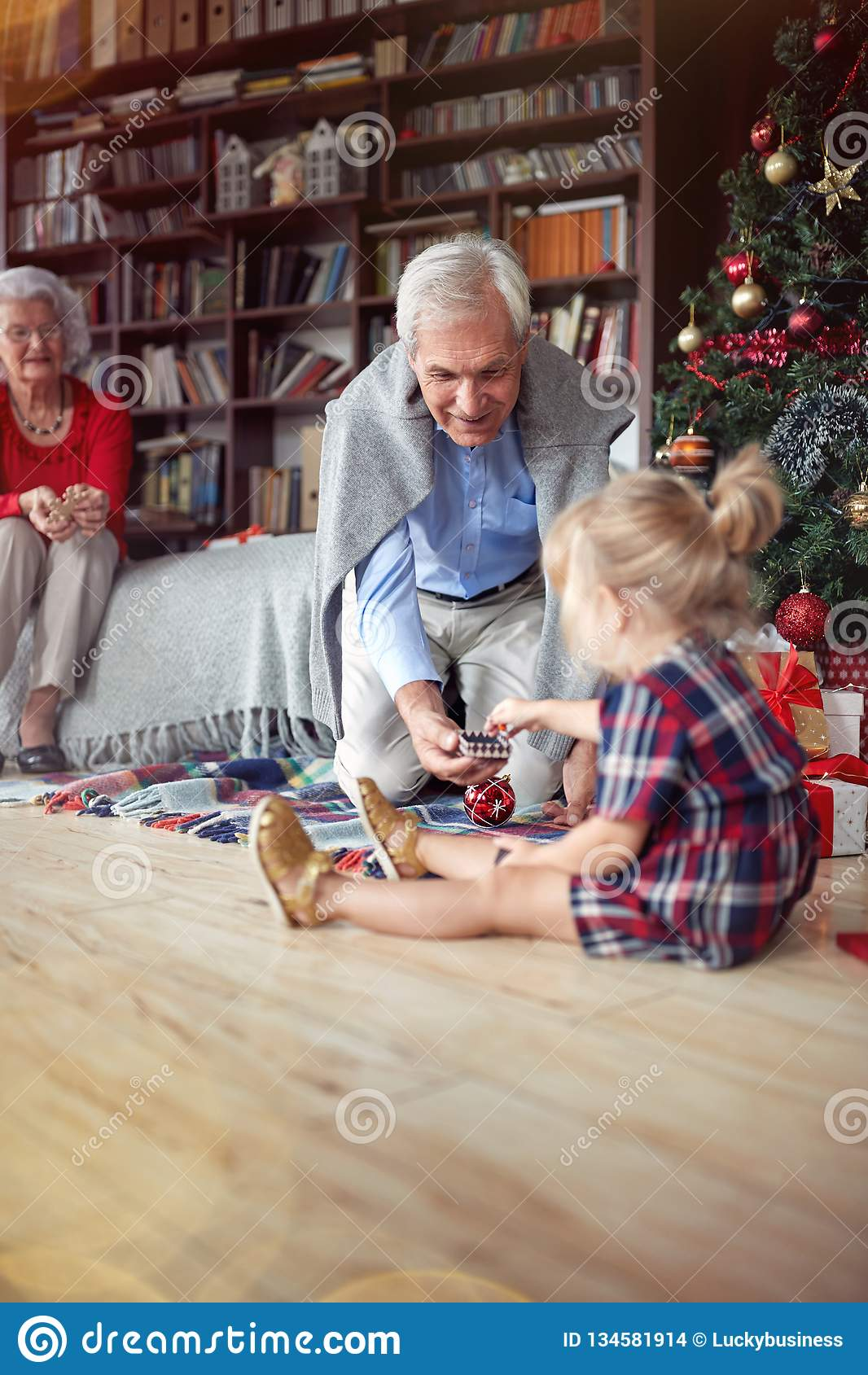 La ragazza è regalo di Natale aperto davanti ad un albero decorato di natale con il nonno
