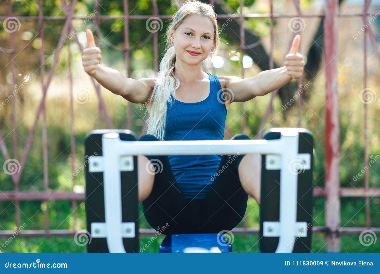 La ragazza adatta in camicia blu e ghette in una palestra del parco mostra il pollice, esaminante la macchina fotografica e sorri