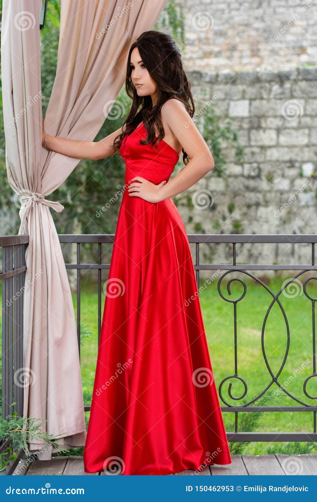 La ragazza affascinante in vestito rosso che posa e tiene una mano sulle anche davanti al recinto ed alle tende del ferro nel gia