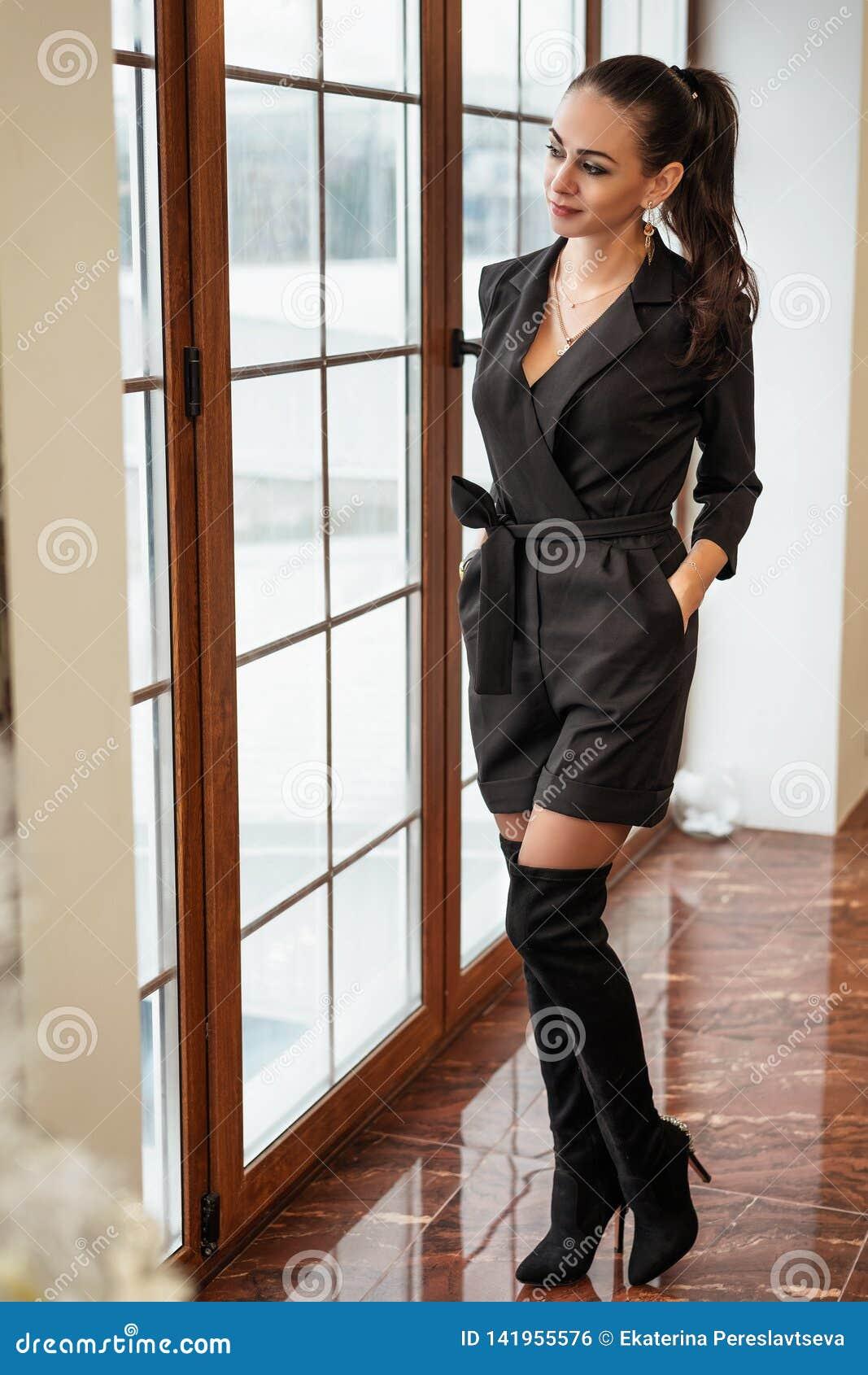 La ragazza alla moda sta alla finestra e sembra i vestiti alla moda