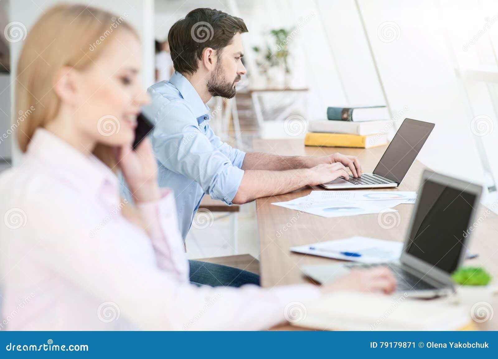 La ragazza allegra ed il tipo stanno usando la tecnologia moderna
