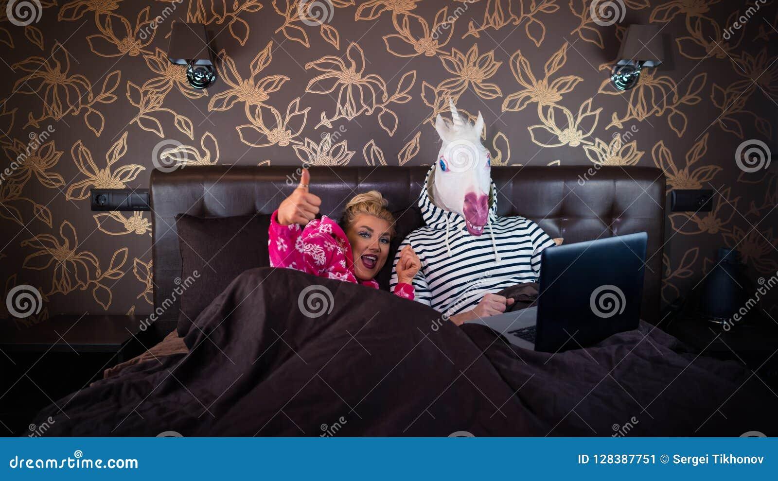 La ragazza allegra mostra i pollici sul gesto e la menzogne sul letto con il ragazzo divertente