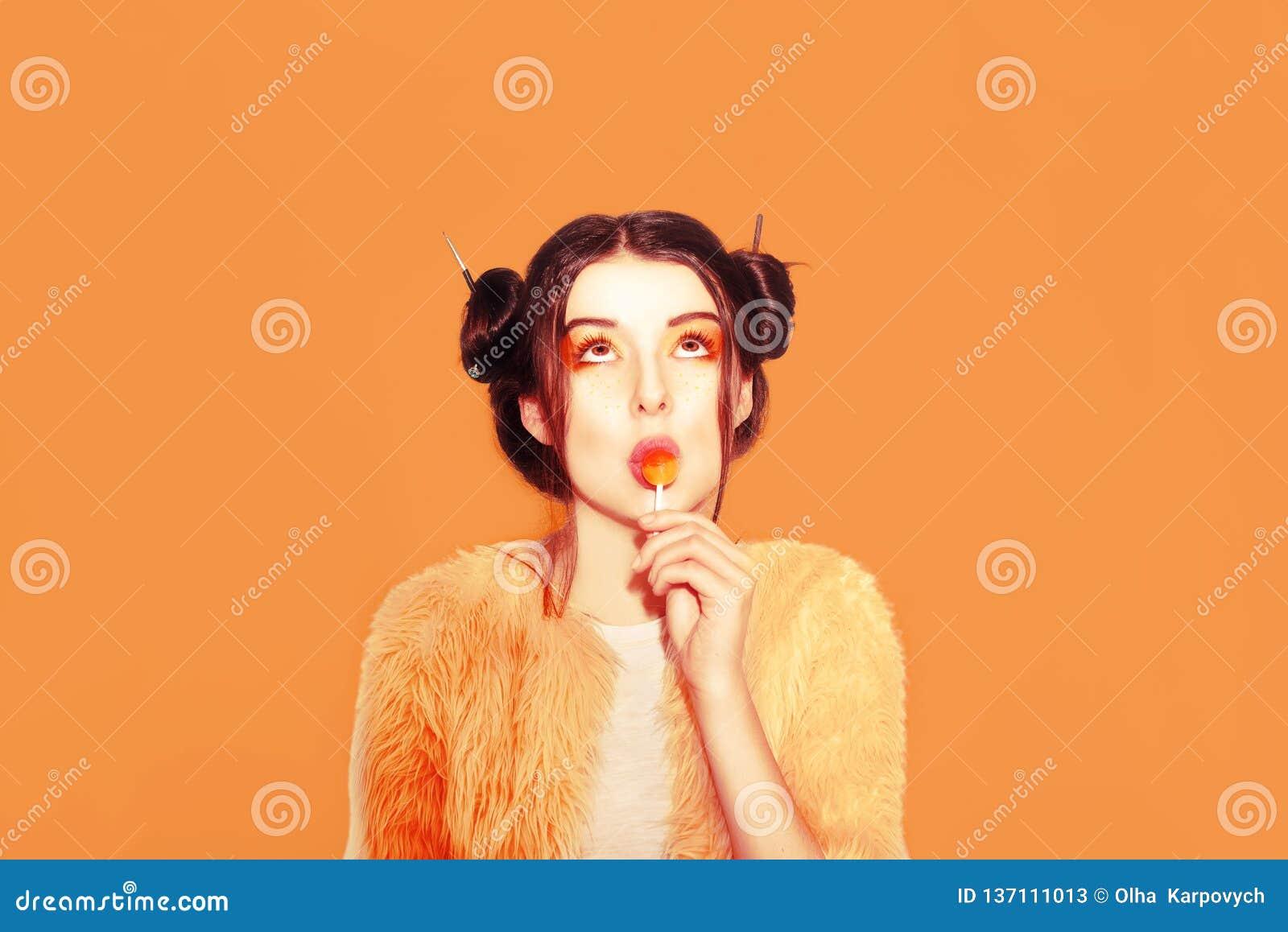 La ragazza in arancia con i panini di vittoria mangia Chupa Chups Ritratto di una ragazza graziosa che mangia lecca-lecca sopra f